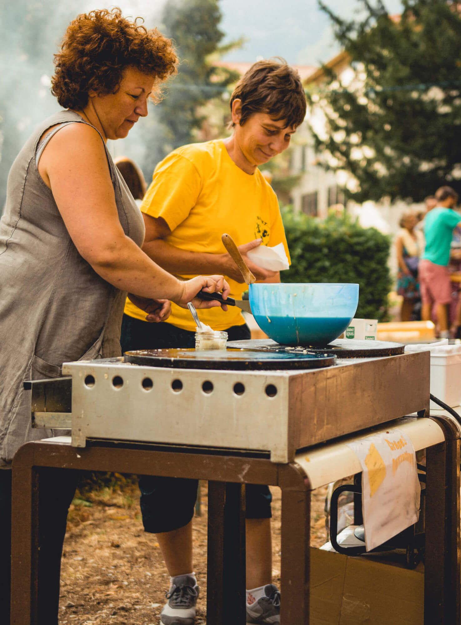 Zwei Frauen bereiten Crêpes auf einem Markt zu.