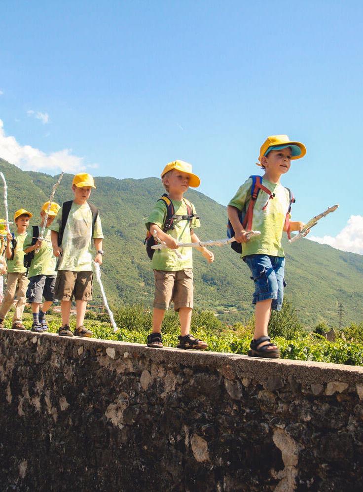 Eine Gruppe kleiner Jungs läuft über eine Mauer. Sie Tragen alle eine gelbe Basecap, ein grünes T-Shirt und einen Wanderstock.