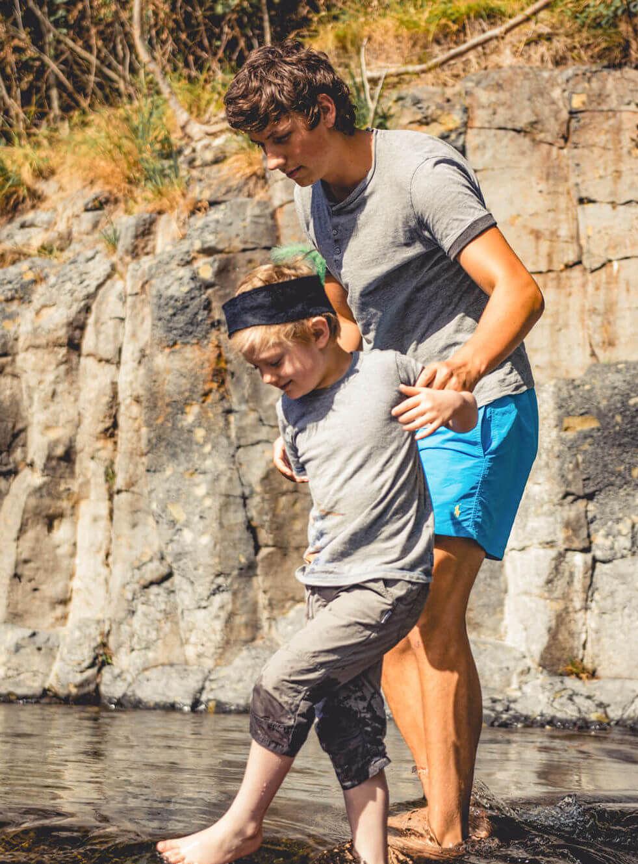 Ein Betreuer und ein Junge stehen im Wasser. Der Betreuer hilft dem Jungen dabei, durch das Wasser zu laufen.
