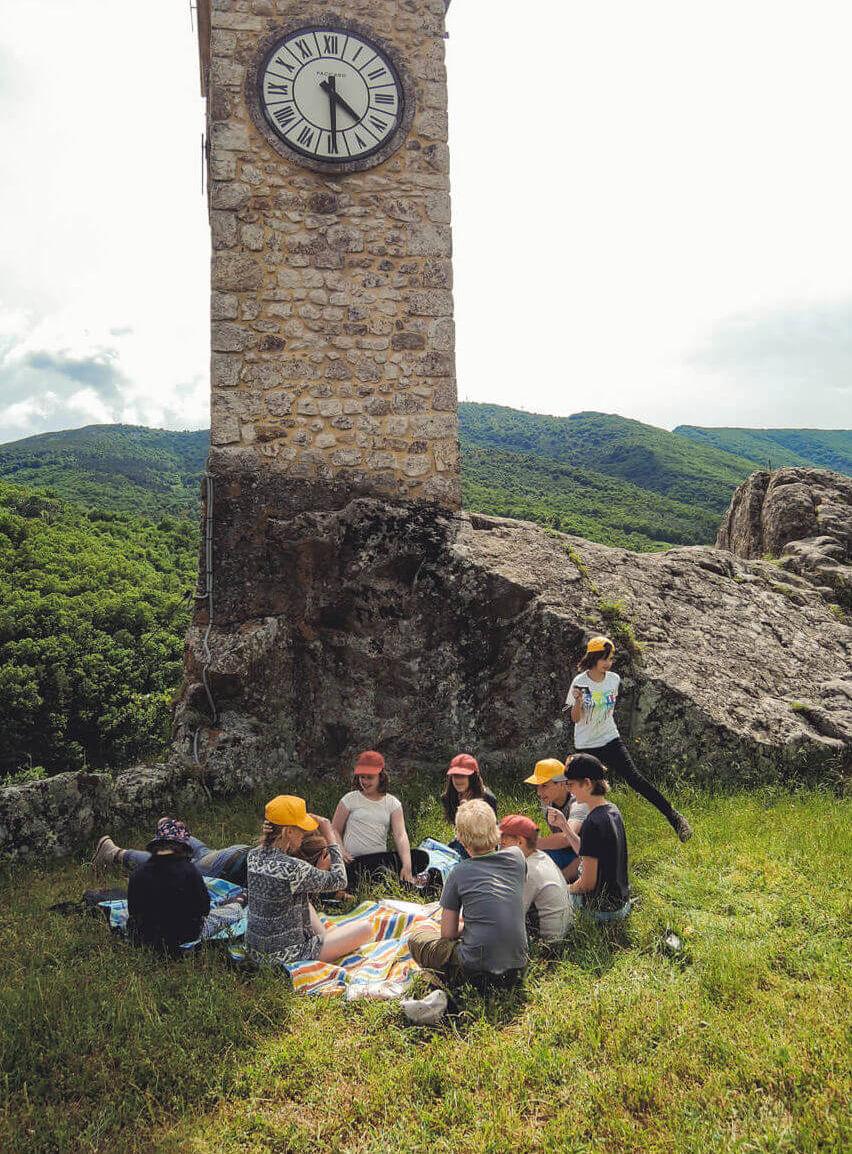 Eine Gruppe von Kindern und Jugendlichen sitzt quatschend an einem altem Kirchturm aus Stein. Der Turm ist in in einen Felsen gebaut worden.