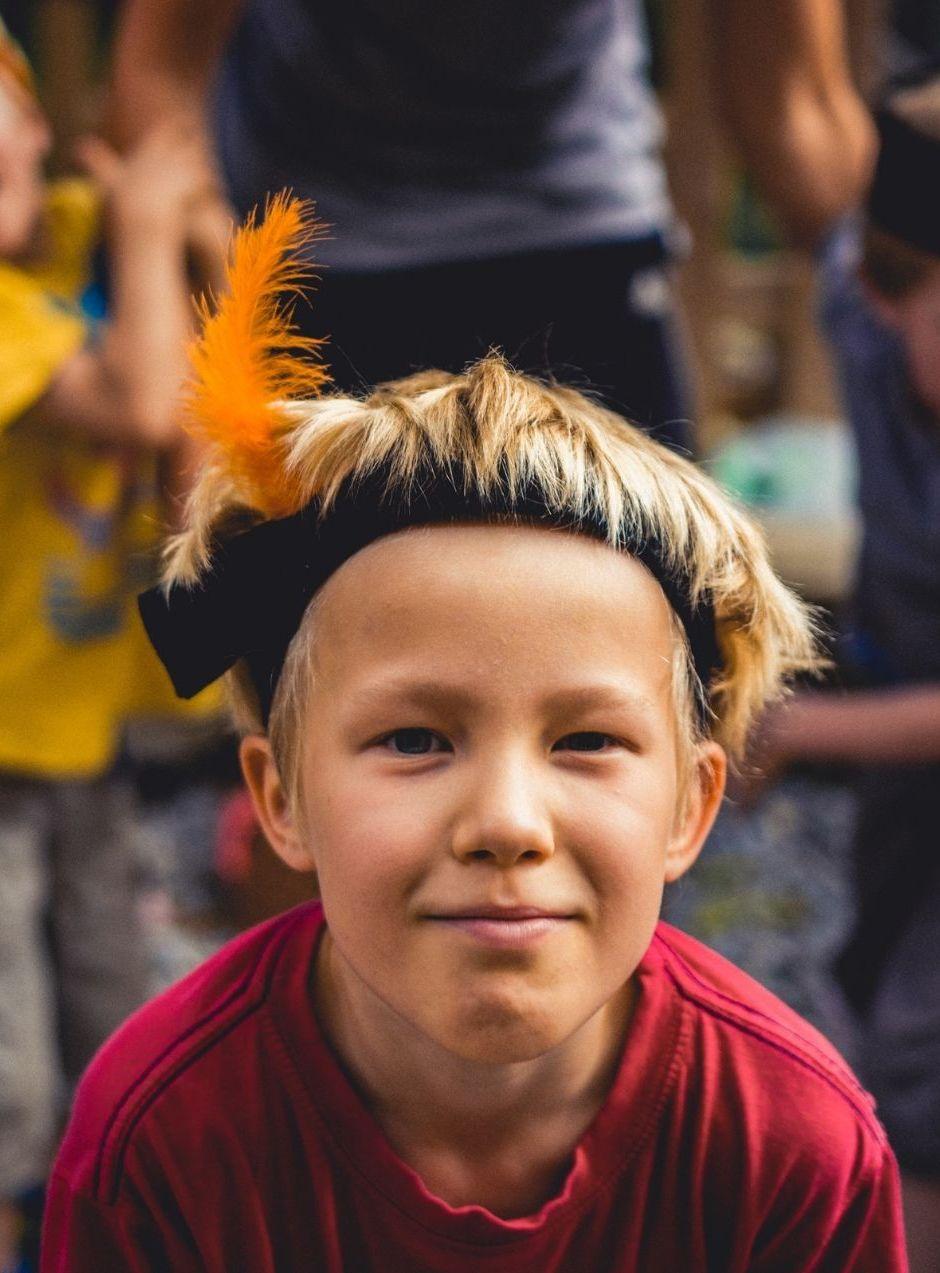 Ein Junge mit bunter Feder auf dem Kopf