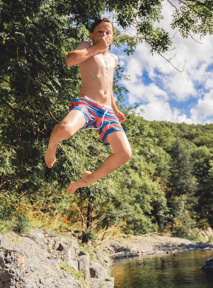 Junge springt an einem Fluss in das Wasser