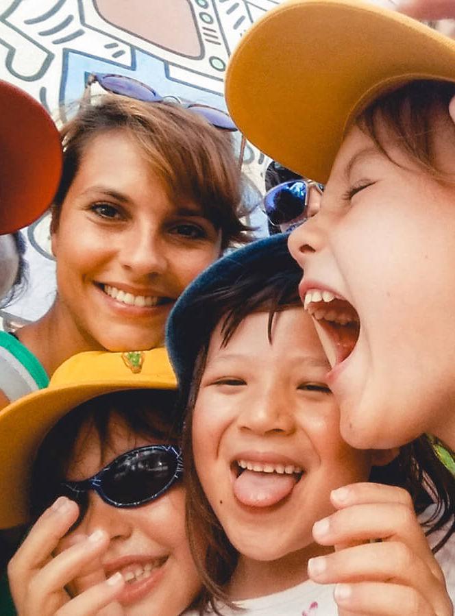 Betreuerin mit drei Kindern, die gemeinsam in die Kamera grinsen.