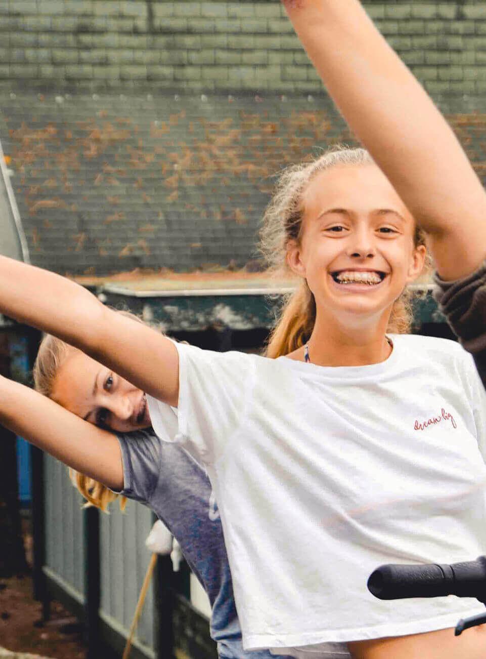 Zwei jugendliche Mädchen stehen hintereinander und strecken lachend die Arme in die Luft. Beide strahlen vor Freude.