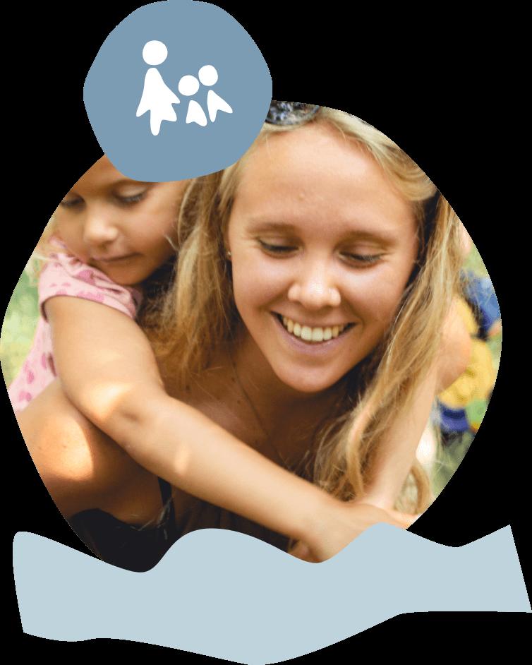 Eine Betreuerin trägt ein Kind auf dem Rücken. Beide lachen.